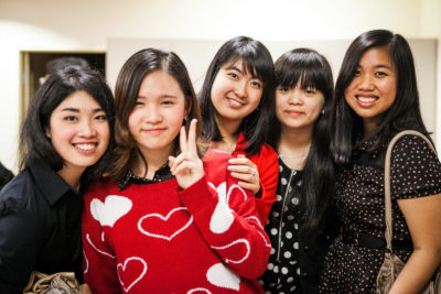 A photograph of a group of five girls at a dinner event